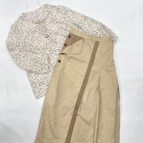 白地ピンク、黒柄ボウタイブラウスとベージュサイドボタン付きスカートのコーディネート